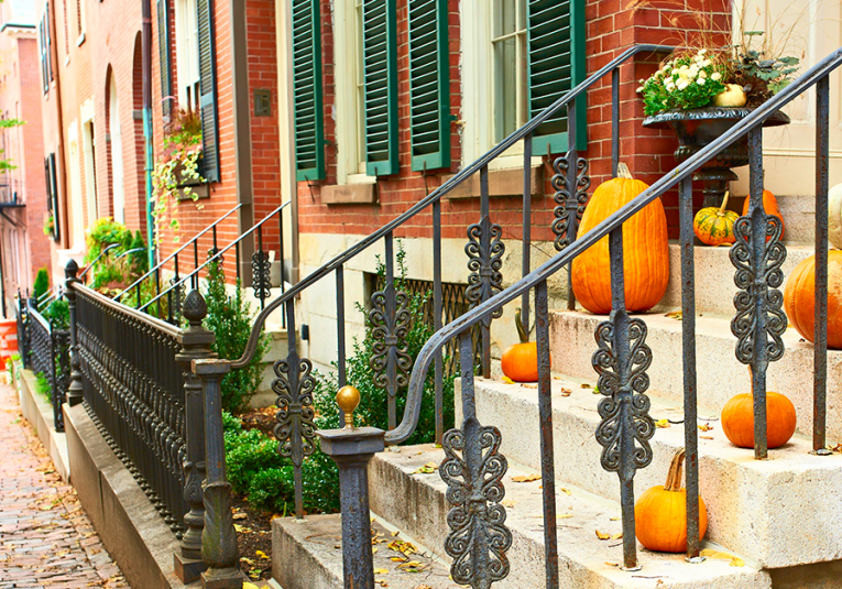 staircase with pumpkins on the steps outside of brick building