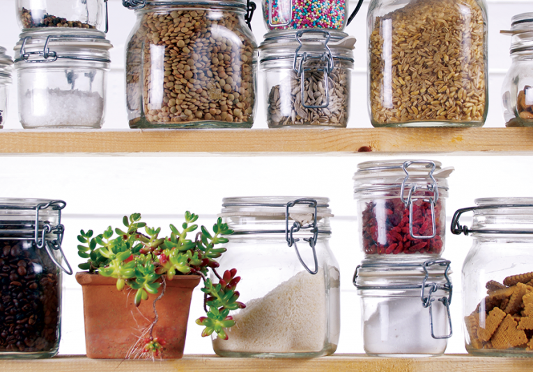 small non perishable foods in clear glass jars next to a plant